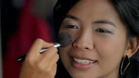 A young beautiful Asian woman having makeup applied, the makeup artist is applying blush or foundation with a brush on her face.