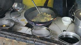 A cook makes delicious Thai food in a wok in northern Thailand.