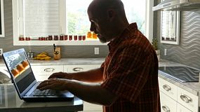 A man checks e-mails in a hurry prior to starting his busy work day.