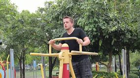 A young man begins exercising at a local park.
