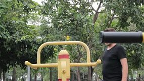 A young man begins working out on the exercise equipment at a local park.