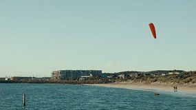 A man taking off from shore on his kite surfboard at a beach in Perth, Western Australia.