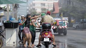 Bangkok, Thailand - April 14, 2014: A man with his child on a scooter stopping to get water splashed on them during the Songkran Festival water fights in Thailand.