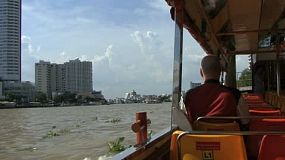 A foreign tourist enjoys taking pictures from his river boat as it cruises down the mighty Chao Phraya river in Bangkok, Thailand.