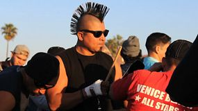 A man with a crazy Mohawk hairdo plays his cowbell at the Venice Beach Drum Circle in Los Angeles.