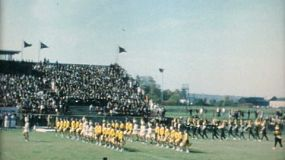 Cheerleaders and marching bands march onto the football field before the big game in the Fall of 1961.