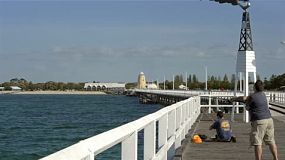 Man casting his fishing line off the busselton jetty, in the south west of australia.