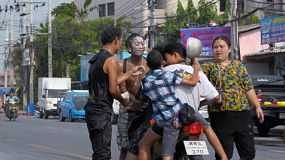 Bangkok, Thailand - April 14, 2014: Young men on a motorbike getting stopped and splashed with water during a water fight as part of the annual Songkran Festival in Thailand.