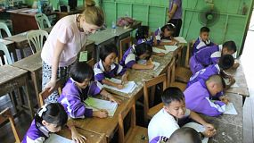 A female young adult on an overseas missions trip teaches Asian children English in Chiang Rai, Thailand.