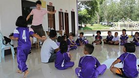 A group of young adult overseas missionary play a fun game of Duck Duck Goose with a class of Asian children on a special outing in Chiang Rai, Thailand.