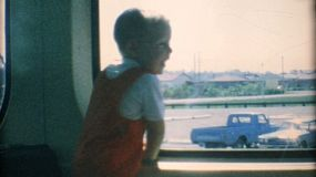 A cute little blond haired boy excited to ride the train with his mom in the summer of 1967.