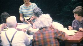 A mom serves delicious birthday cake to her family at the big summer reunion in 1967.