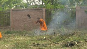 Two monks bravely deal with a brush fire that starts behind the Buddhist temple outside of Bangkok, Thailand.