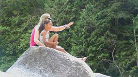 A cute little 9 year old Asian girl enjoys spending time with her Mom while hiking in the woods and discovering a beautiful waterfall on a gorgeous sunny summer day.