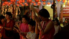 BANGKOK, THAILAND  - FEBRUARY 9, 2013: Mother teaching her son to pray at Wat Mangkon Kamalawat on the eve of Chinese New Year in Chinatown, Bangkok, Thailand.