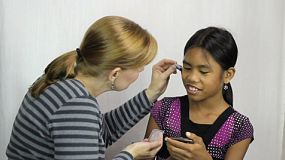 A loving mother applies make up to her 11 year old daughter's face for the first time.