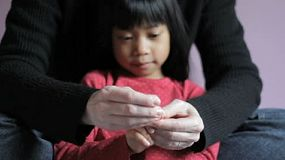 A cute little Asian 5 year old gets her finger nails carefully trimmed by her mother.