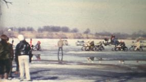 Men and women race fast motorcycles on a frozen lake in the winter of 1970.