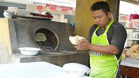 A Muslim man makes traditional naan Tandoori bread in a hot stove oven in Mae Sot, Thailand.