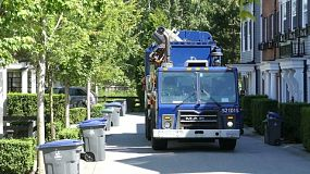 A new modern garbage truck comes to collect the trash in a suburban townhouse community.