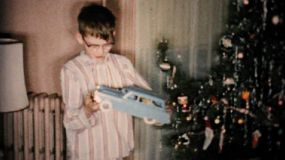 A little boy gets a new toy car while others enjoy spending time together, opening gifts and celebrating Christmas in Cleveland, Ohio in 1954.