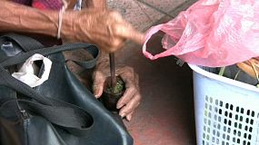 An old Asian lady uses a small bowl to grind her own tobacco down in Bangkok, Thailand.