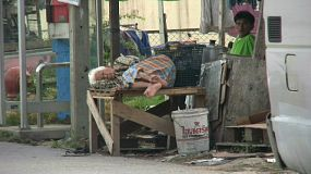 An old Thai lady sleeps beside the busy street on the edge of the slums in Bangkok, Thailand.