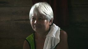 A close up shot of an older Thai lady with white hair visiting with her friends in the slums of Bangkok, Thailand.