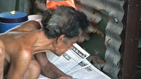 A zoom out shot of an old Thai man reading the newspaper in the slums of Bangkok, Thailand.
