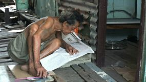An old Thai man reads the morning newspaper in the slums of Bangkok, Thailand.