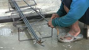 An old Asian man ties wire onto rebar to prepare forms for concrete in Bangkok, Thailand.