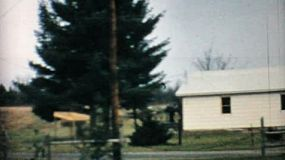 A left to right pan of an old house in the country in 1968.