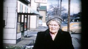 A old lady walks down the sidewalk in the Fall of 1956 looking at the camera and smiling.