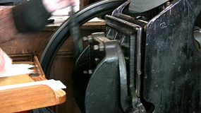 An old style printing press coming to a stop after printing off cards.
