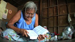 An old Asian woman reads her bible at the community center in the slums of Bangkok Thailand.