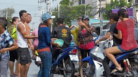 Bangkok, Thailand - April 14, 2014: Passing motorbikes being forced to stop and get splashed by a group of people during the water fights of the annual Songkran Festival in Thailand.