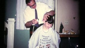 A loving father gives his teenage son a cool hair cut in the Fall of 1972.