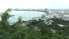 A pan shot of Pattaya bay and Pattaya city in Thailand on a hazy day near dusk.