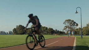 Various people passing as they exercise along a bike path along the South Perth foreshore.
