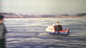 Men and women race fast snowmobiles on a frozen lake in the winter of 1970.