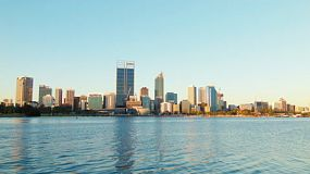 The golden light of the setting sun shining on the Perth City CBD skyline, framed between the clear blue skies and the waters of the Swan River.