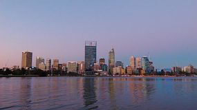 View of the City of Perth from across the Swan River, with the skyline reflecting on the water, in the purple shades of post sunset light on a clear evening.