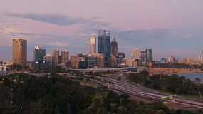 View of the City of Perth with the approaching Kwinana Freeway, in the purple toned light of dusk.