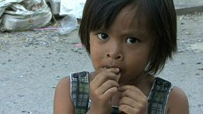 A poor little Thai girl eats dried fish in the slums of Bangkok, Thailand.