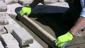 A worker wearing green gloves prepares to install sidewalk bricks on a beautiful sunny day. (HD 1080p30)