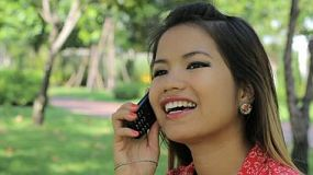 A beautiful Thai girl enjoys talking on her cell phone in the park with some friends.