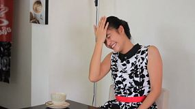 An attractive Asian young adult woman laughs hysterically while spending time in a cafe in Bangkok, Thailand.