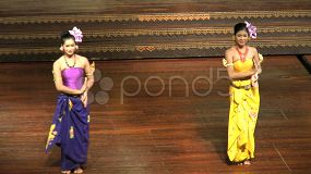 A pair of beautiful Asian female dancers perform a traditional dance on the outdoor stage in Pattaya, Thailand.