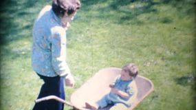 A pretty little girl gets a wheelbarrow ride from her Grandma in the backyard in the summer of 1969.