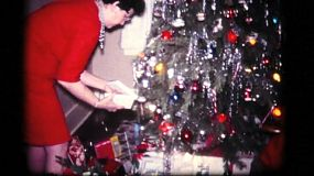 A pretty dressed up Momma checks out her opened presents under the Christmas tree in 1961.